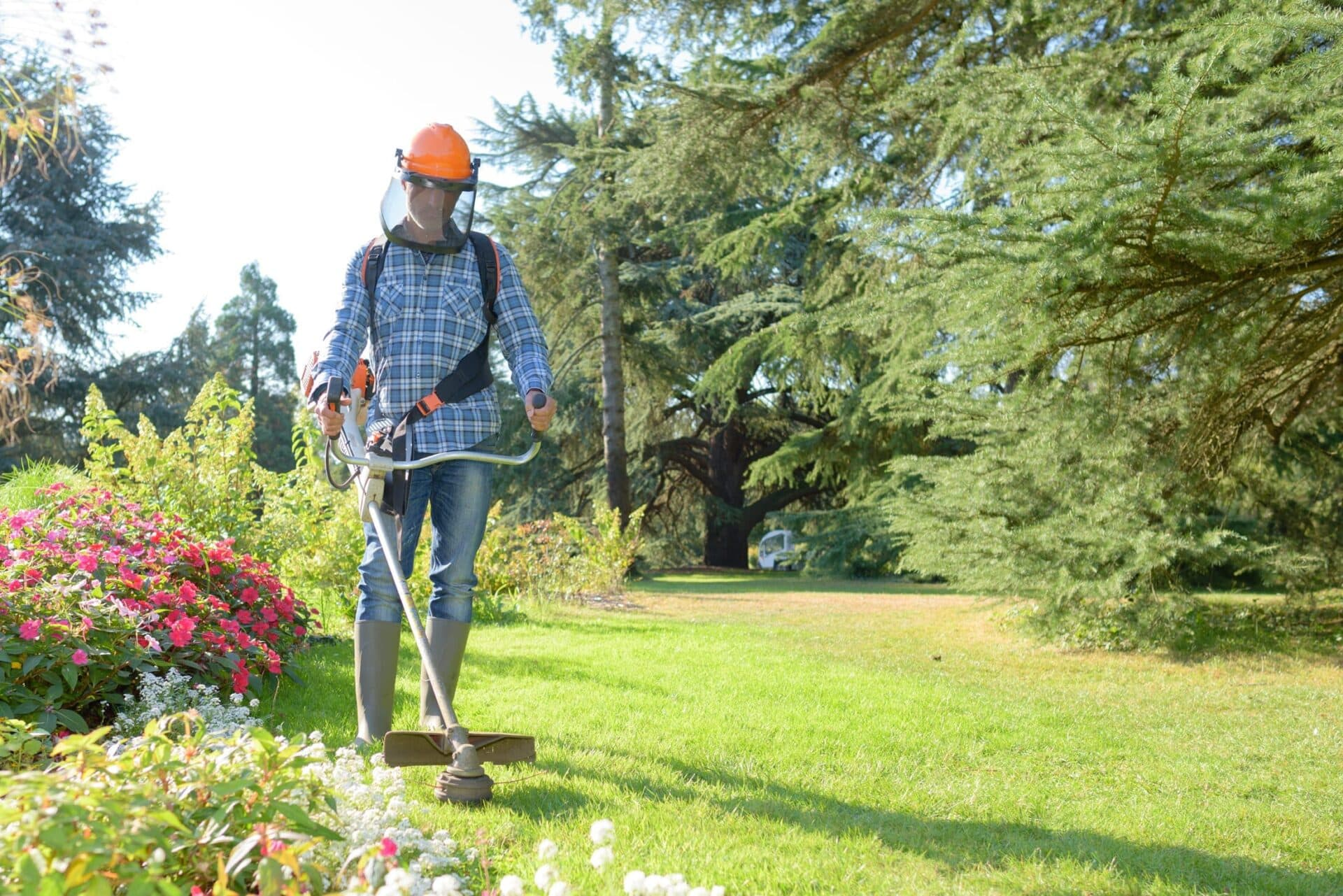 Man in gardening gear and visor performing grounds maintenance with professional lawn mowing tools