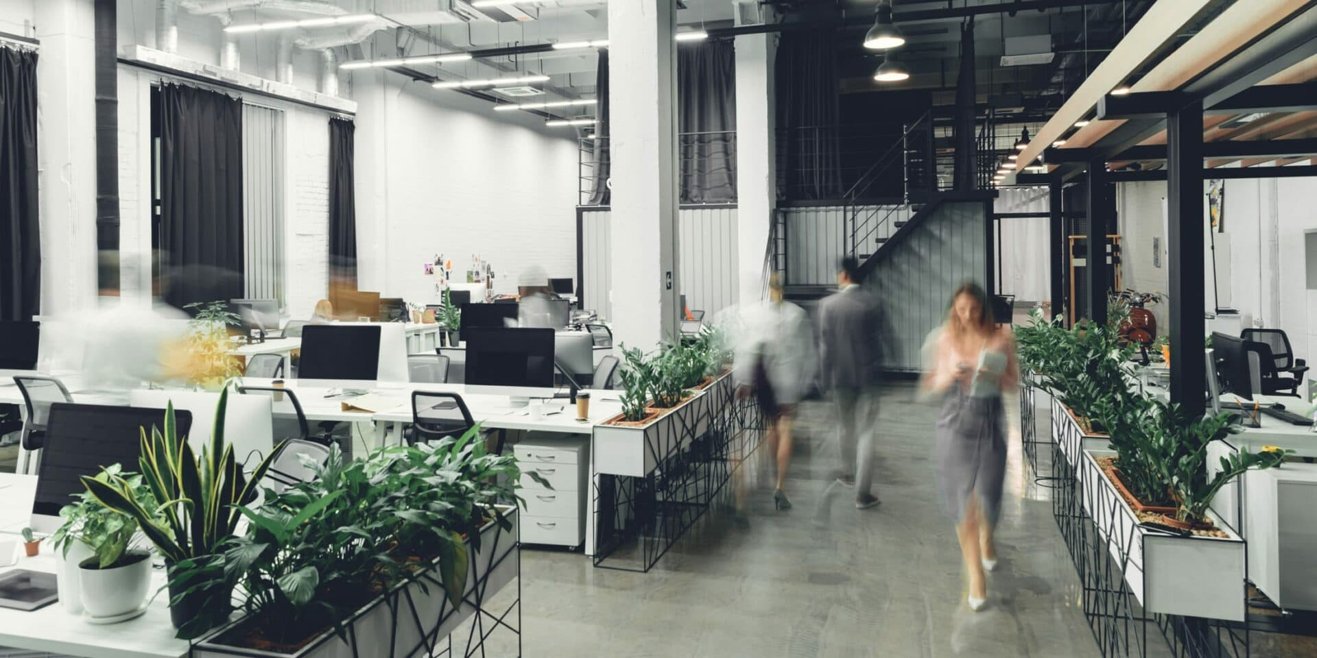 Long exposure shot of office workers walking through open plan office environment