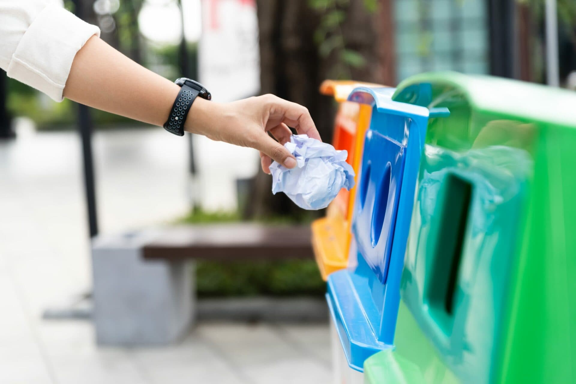 Person using coloured recycling bins to dispose of paper waste